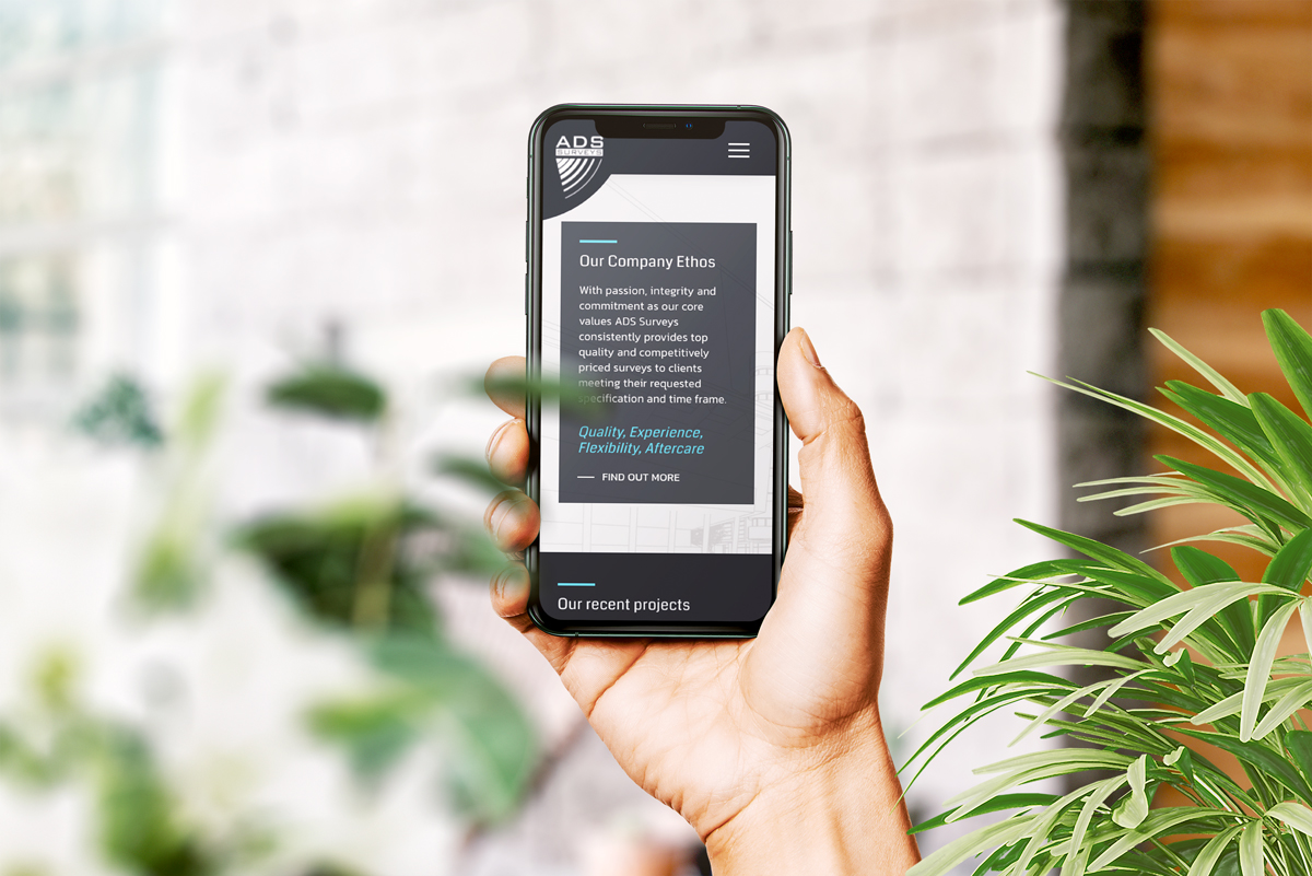 Image of the ADS website mocked up on a mobile phone someone is holding in shot surrounded by plants